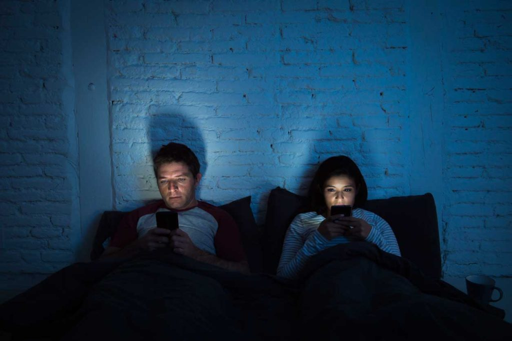 Couple in bed with phones at night