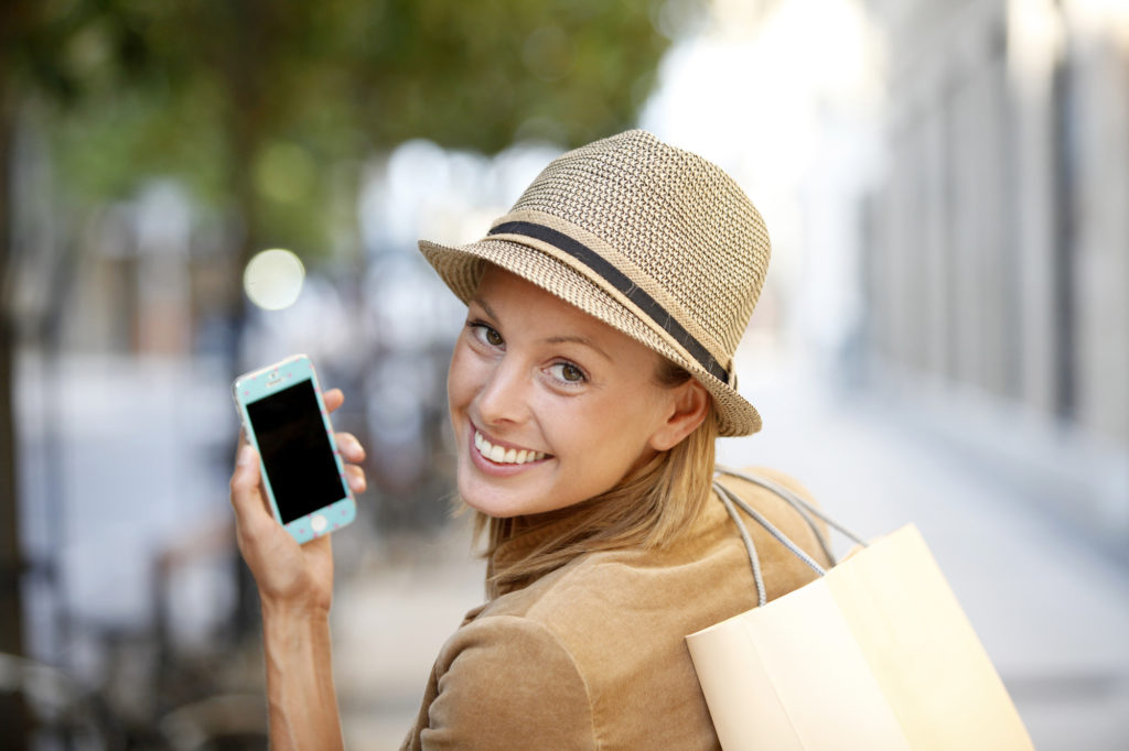 Smiling shopping girl using smartphone in town