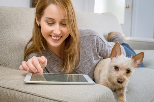 Woman on her table at home with cute dog