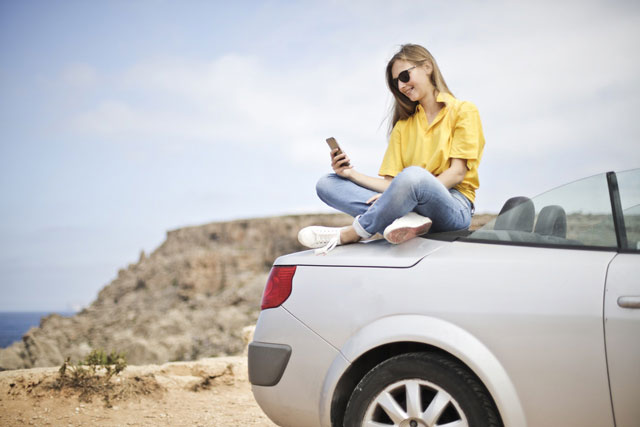 Girl on the beach with her car and phone