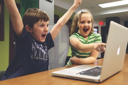 Two children cheering with their laptop